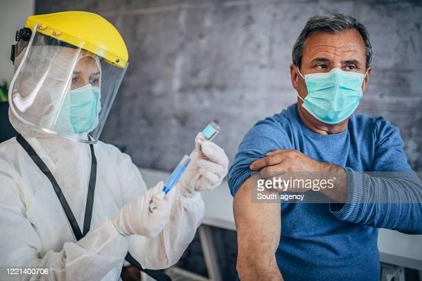 maschio anziano che riceve il vaccino contro il coronavirus covid-19 - dose foto e immagini stock