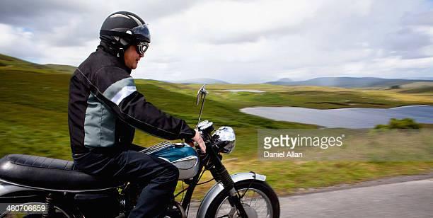 Senior male riding motorbike through rural landscape