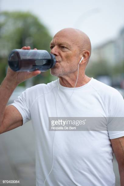 Ältere männliche Läufer auf Bürgersteig mit Wasserflasche