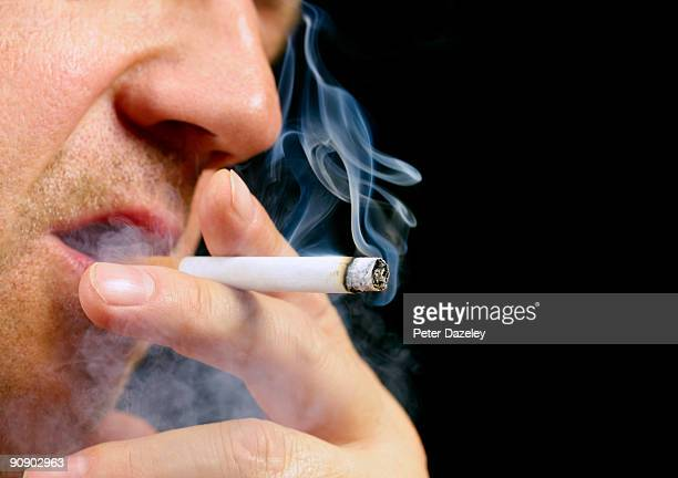 Senior male smoking cigarette on black background