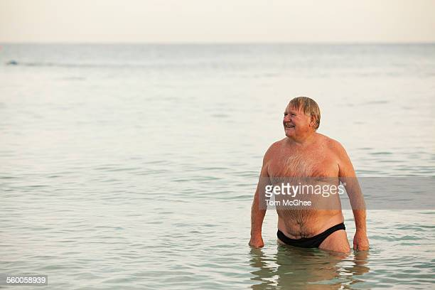 Senior male standing in water at beach