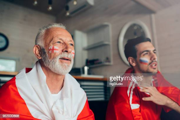 senior male supporting uk soccer team watching a game on tv with russian team fan - fan enthusiast stock photos and pictures