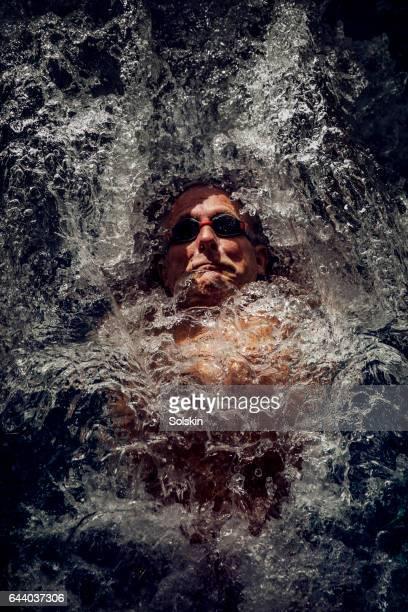 senior male swimmer doing backstrokes, water splashing