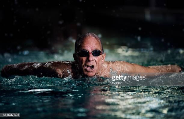 senior male swimmer doing breaststroke - uithoudingsvermogen stockfoto's en -beelden