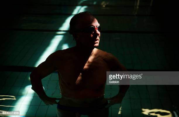 senior male swimmer standing in swimming pool