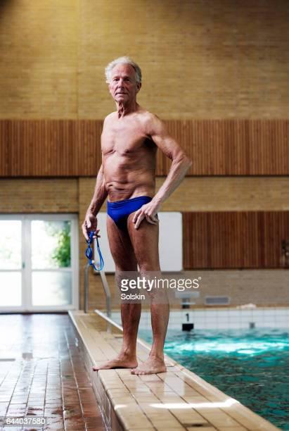 Senior male swimmer standing on swimming pool edge