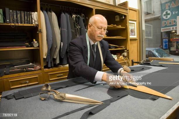 Senior male tailor working in shop