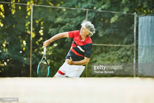 senior male tennis player hitting slam during tennis match - racquet stock pictures, royalty-free photos & images