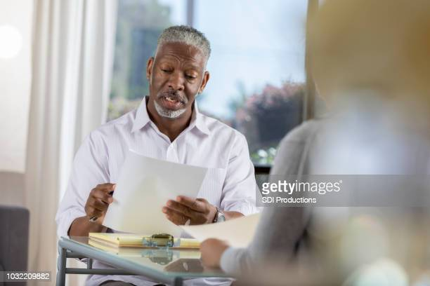 senior male therapist asks new client intake questions - form document stock photos and pictures