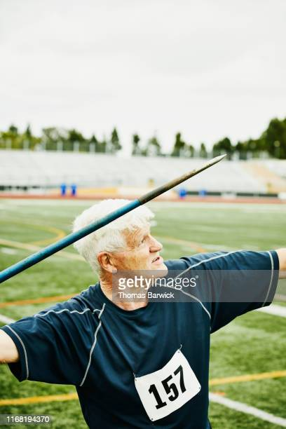 senior male track and field athlete throwing javelin - men's field event stock pictures, royalty-free photos & images