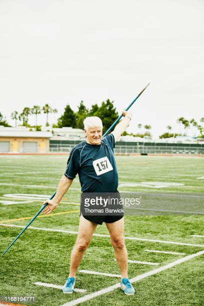 senior male track and field athlete warming up with javelin on field - men's field event stock pictures, royalty-free photos & images