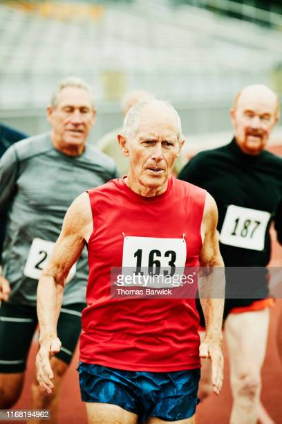 senior male track athlete leading distance race on track - 陸上競技大会 ストックフォトと画像