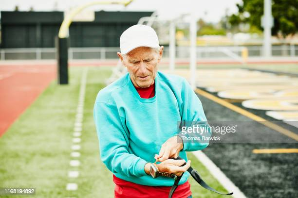 Senior male track athlete putting on fitness watch before working out