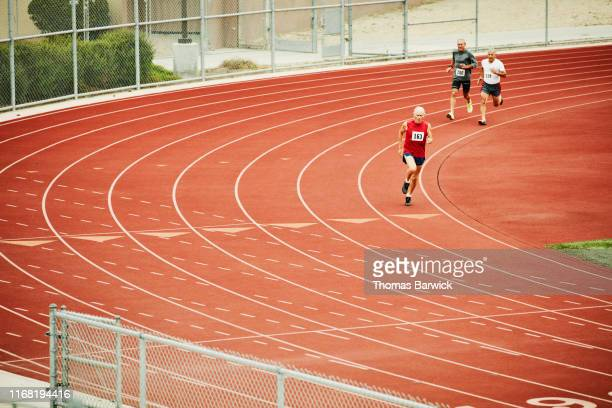 senior male track athletes running distance race on track - forward athlete stock pictures, royalty-free photos & images