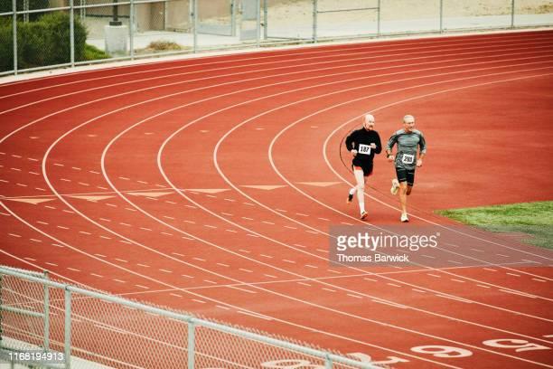 Senior male track athletes running distance race on track