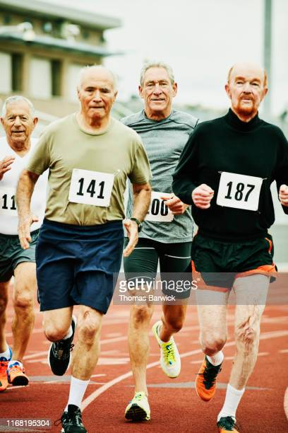 senior male track athletes running distance race on track - 陸上競技大会 ストックフォトと画像