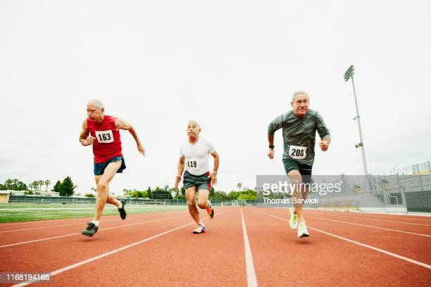 senior male track athletes running sprint on track during race - chance stock pictures, royalty-free photos & images
