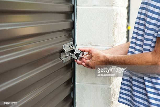 senior male unlocking a storage warehouse - self storage stock pictures, royalty-free photos & images