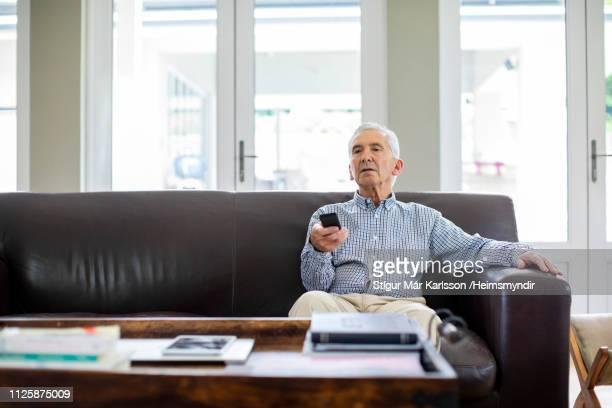 senioren männlich mit fernbedienung fernsehen - einzelner senior stock-fotos und bilder
