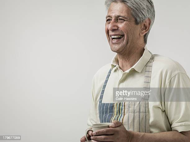 senior male wearing apron - apron stock pictures, royalty-free photos & images