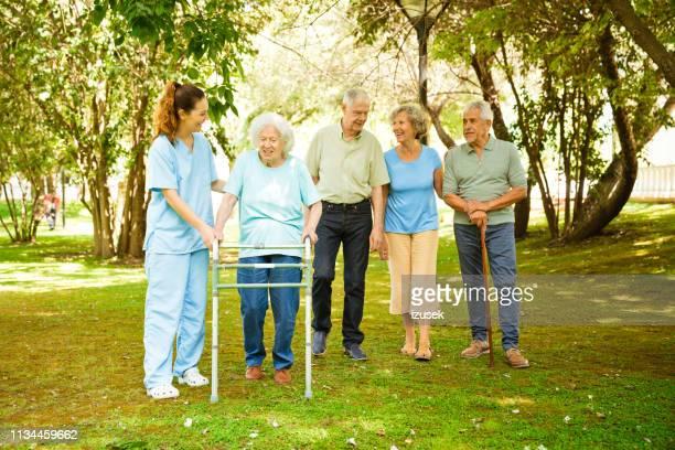 senior mannetjes en vrouwtjes met verpleegkundige op achtertuin - izusek stockfoto's en -beelden