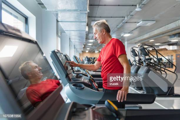 senior man adjusting speed on treadmill at rehab - drug rehab stock pictures, royalty-free photos & images