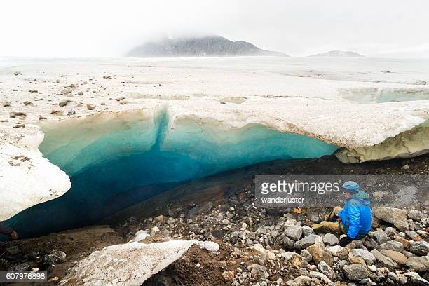 Senior man admires ice cave in Alaska