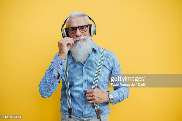 senior man against yellow background - people stock pictures, royalty-free photos & images