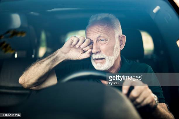 senior man almost falls asleep while driving. - scratching stock pictures, royalty-free photos & images