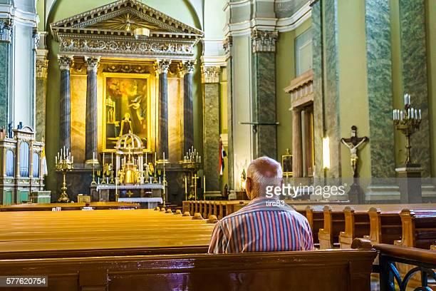 Senior man alone in catholic church