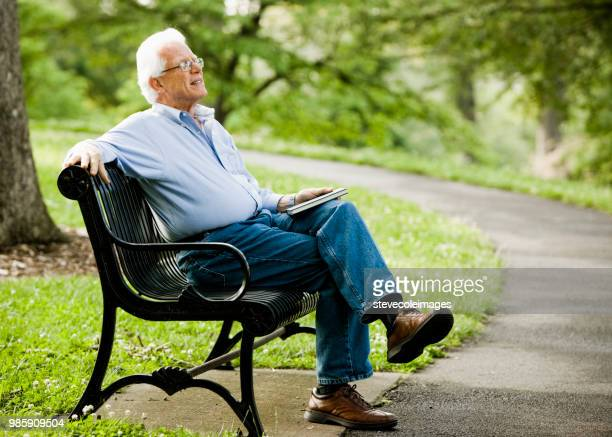 Senior man alone on park bench.