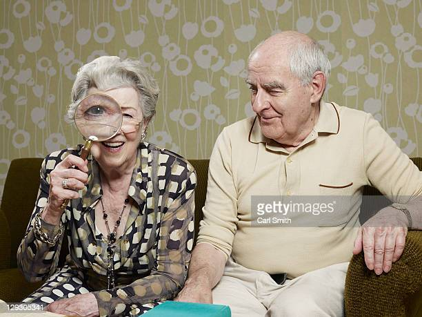 Senior man amused as senior woman magnifies appearance of her eye with magnifying glass