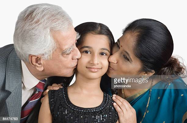 senior man and a mature woman kissing their granddaughter - indian girl kissing stock photos and pictures