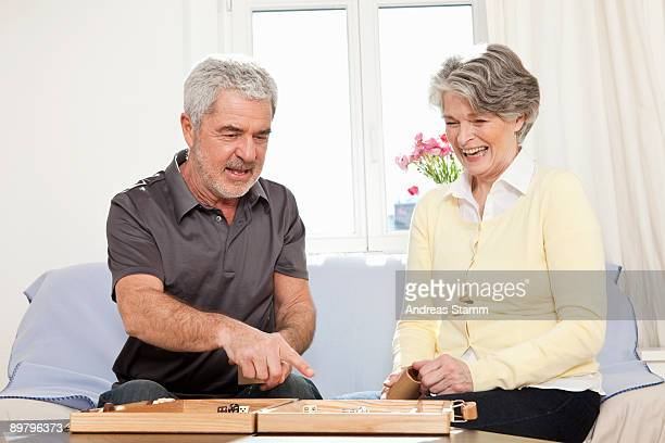 A senior man and a senior woman playing backgammon