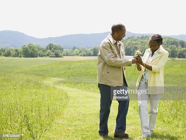 senior man and a senior woman walking in a field - gras bildbanksfoton och bilder