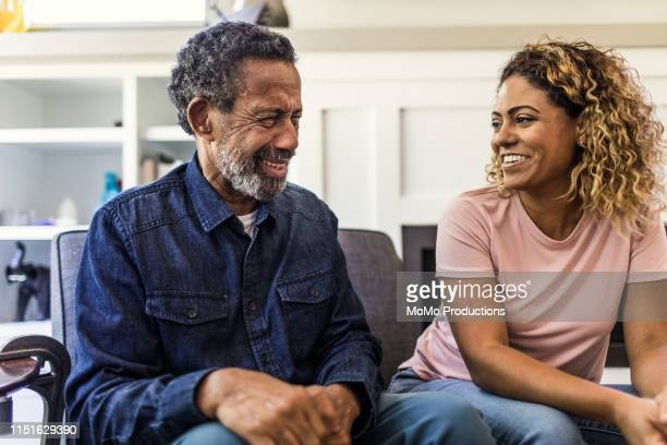 senior man and adult daughter talking on couch - daughter stock pictures, royalty-free photos & images