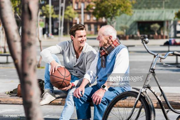 Senior man and adult grandson with basketball talking on a bench