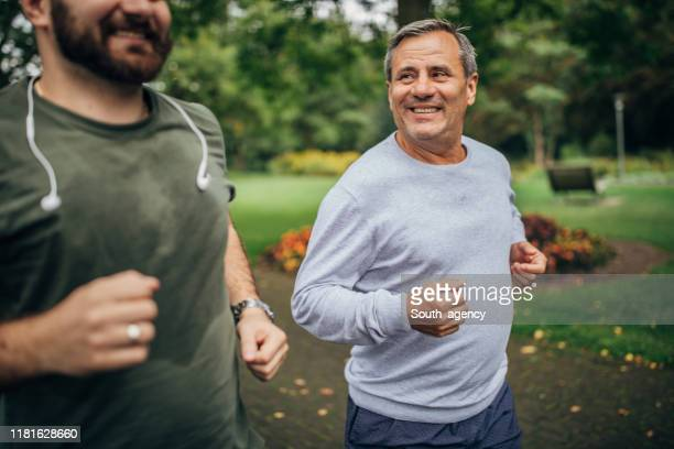 senior man and adult son jogging in park - mid adult stock pictures, royalty-free photos & images