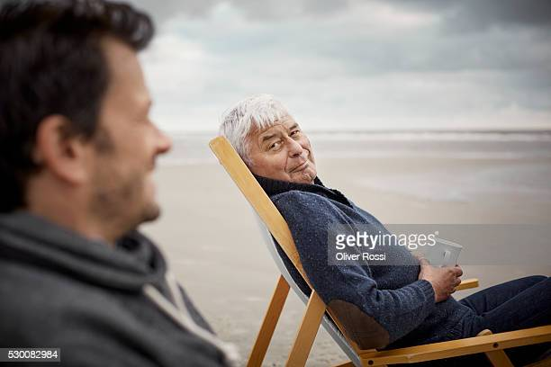 Senior man and adult son on the beach relaxing in deckchairs