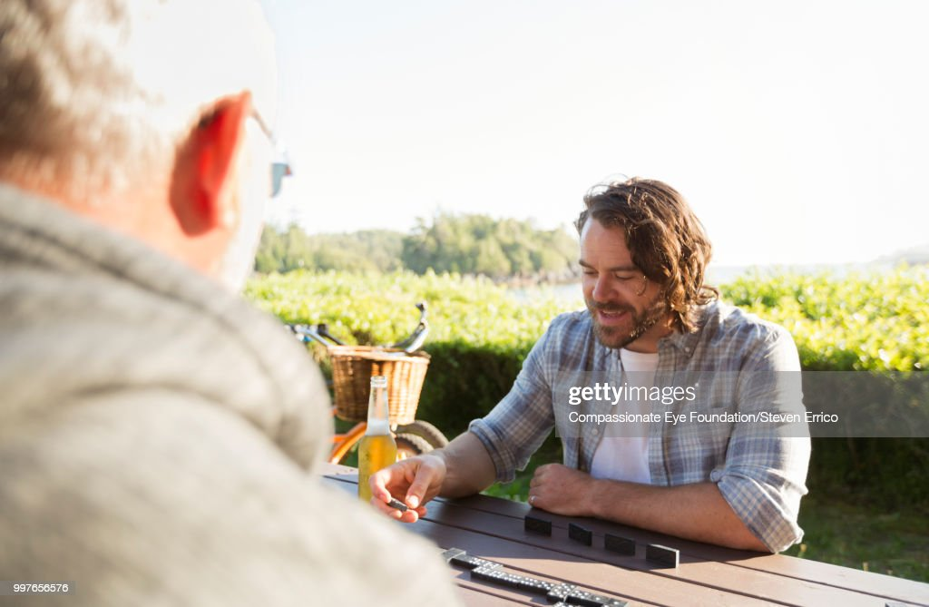 Senior man and adult son playing dominoes at campsite picnic table : Stock Photo