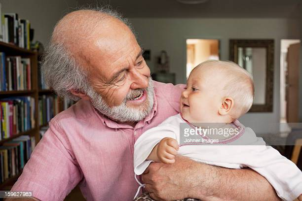 Senior man and baby smiling at home