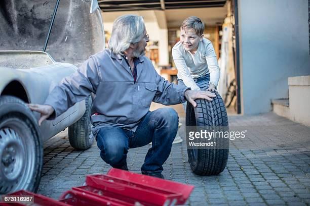 Senior man and boy changing car tire