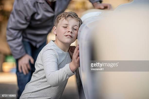 Senior man and boy examining old car together