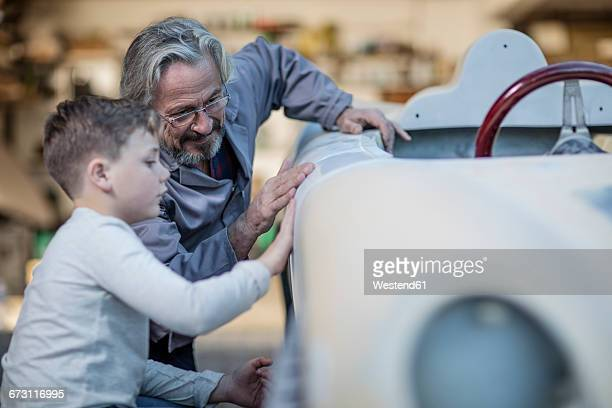 senior man and boy examining old car together - vintage car stock pictures, royalty-free photos & images