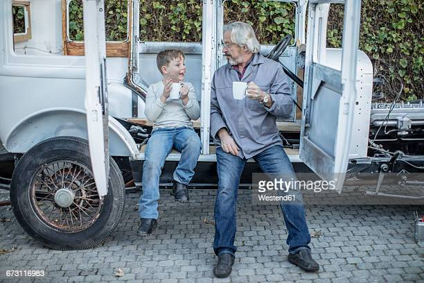 senior man and boy having a coffee break at vintage car - vintage auto repair stock pictures, royalty-free photos & images