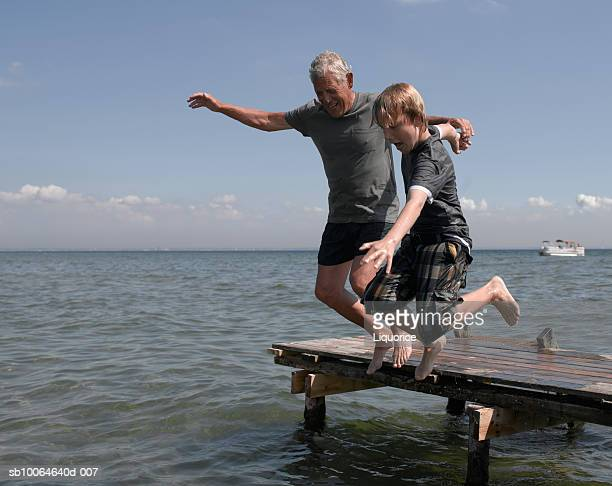 Senior man and boy (10-11) leaping off jetty