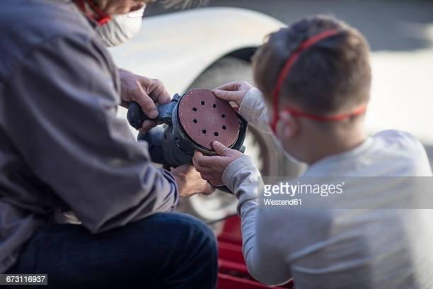 Senior man and boy looking at grinding machine at car