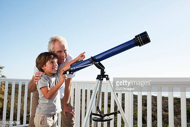senior man and boy with a telescope - telescope stock pictures, royalty-free photos & images