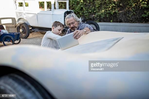Senior man and boy with digital tablet at car