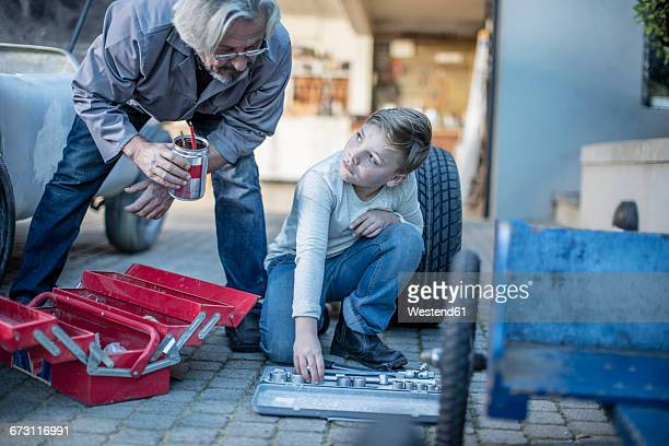 Senior man and boy with tools at car